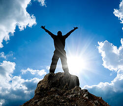 Man standing atop a mountain with his arms spread wide